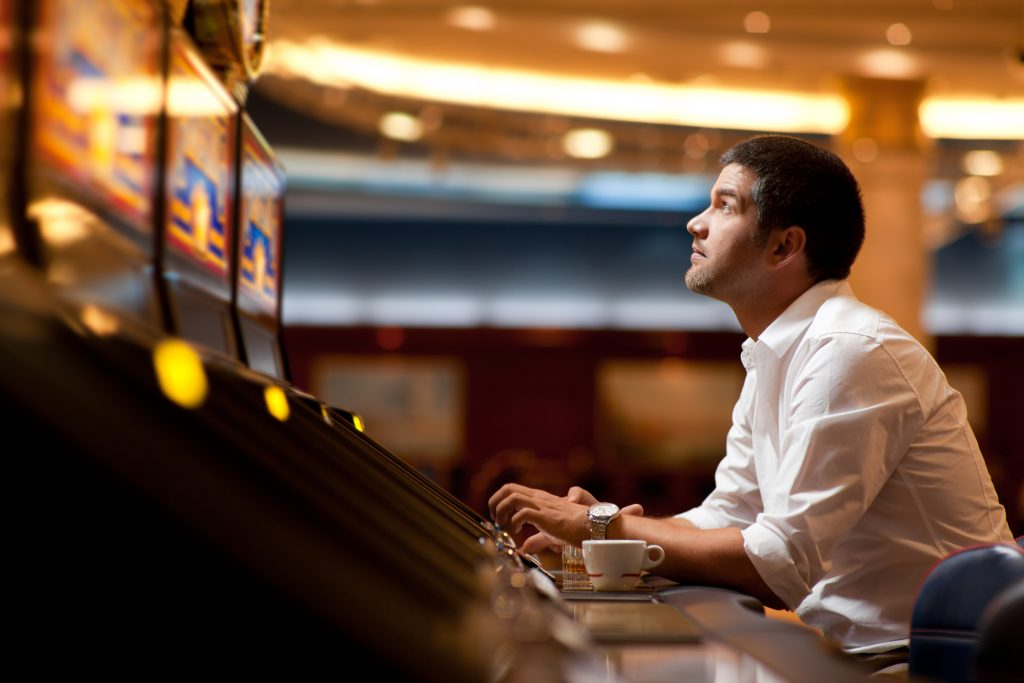 Man playing the pokies at a casino