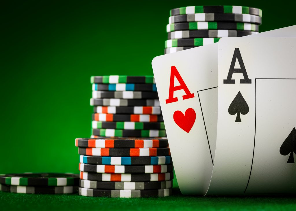 stack of baccarat casino chips and two aces